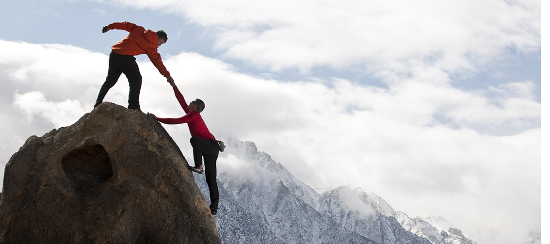 Mountaineer giving helping hand to colleague reaching top of mountain